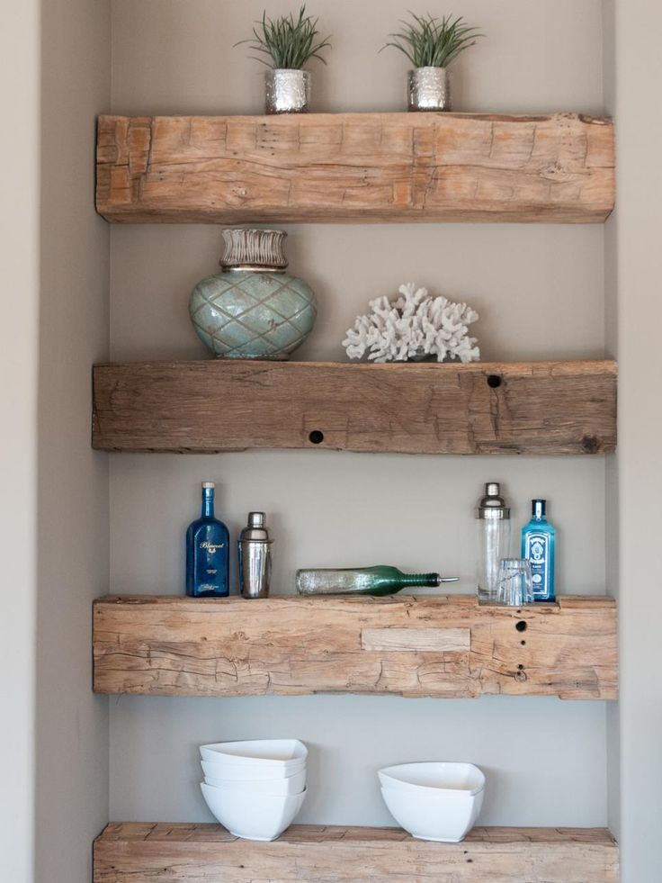 A niche in the wall allows for a stylish space for displaying art and decor. Built-in natural wood shelves add a rustic feel to the foyer.