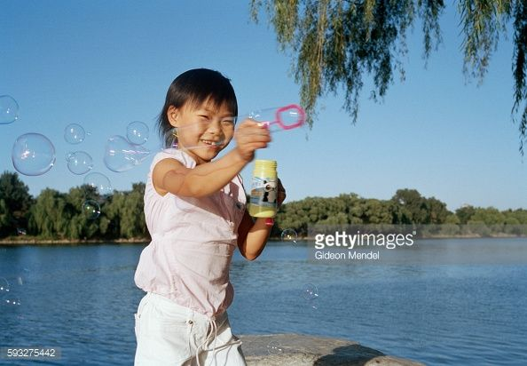 Young gymnast Zhao Chaoyue (8) plays with bubbles during a family trip to Yuyuantan Park. This was during a weekend visit to her family, who live in a small two-roomed apartment on the outskirts of Beijing. She is a student at the Shishahai Sports School, one of the most successful training venues in China, where young gymnasts and other sports trainees live and start intensive training from the age of five.