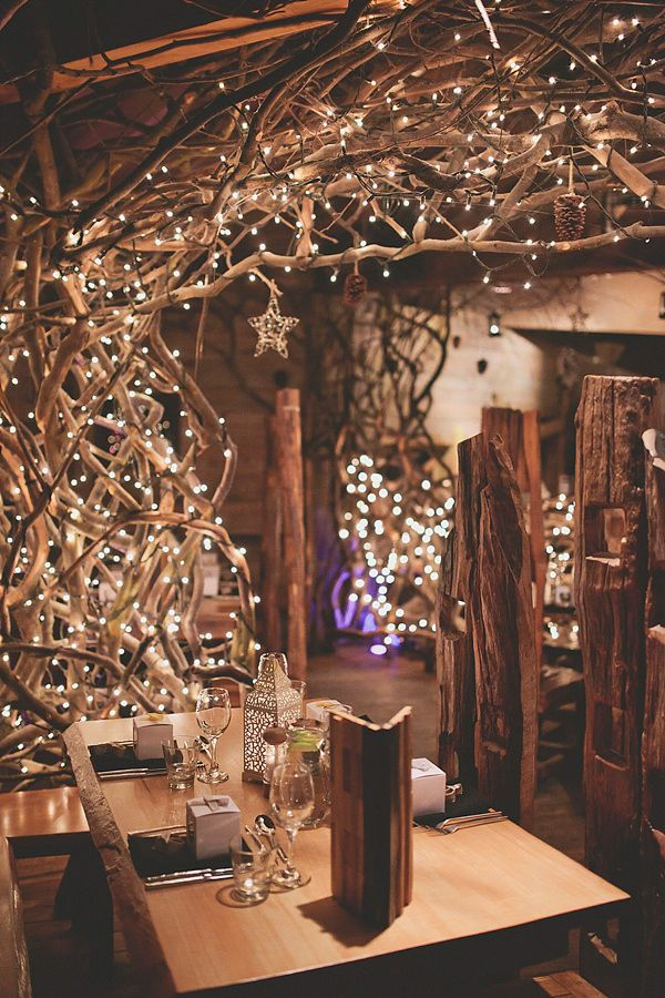 String lights weaved through the twists and turns of branches creates a fanciful arch above this wedding guestbook table.
