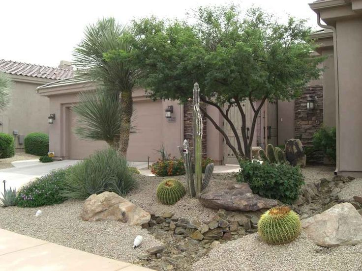 Arizona desert front yard xeriscaping idea with a fake dry for Landscaping rocks and plants