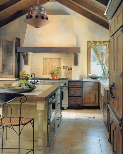 Spanish-Moroccan kitchen has latticework and cabochon nails on carcassone-inspired cabinetry; brooksBerry