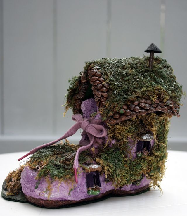 Shoe fairy house for the garden. Moss, stones and more decorate this lovely treasure.