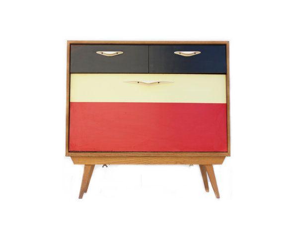 Kommode, in Holz gefertigt mit Resopal Frontseite (schwarz, gelb, rot), original aus der Zeit der 1950er Jahre, in sehr gutem Vintage Zustand.  Höhe 77 cm Länge 79 cm Tiefe 34 cm