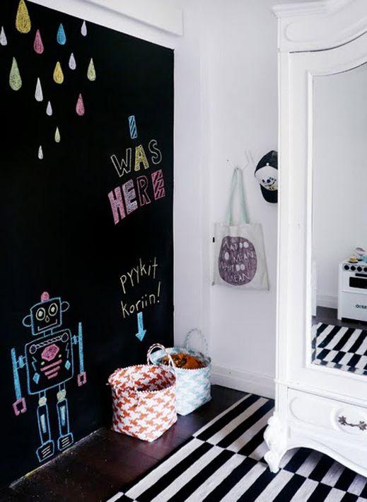 Eine schwarze Wand im Kinderzimmer mit Tafelfarbe. Der alte, weiße Kleiderschrank und der schwarz-weiß gestreifte Teppich passen toll dazu.