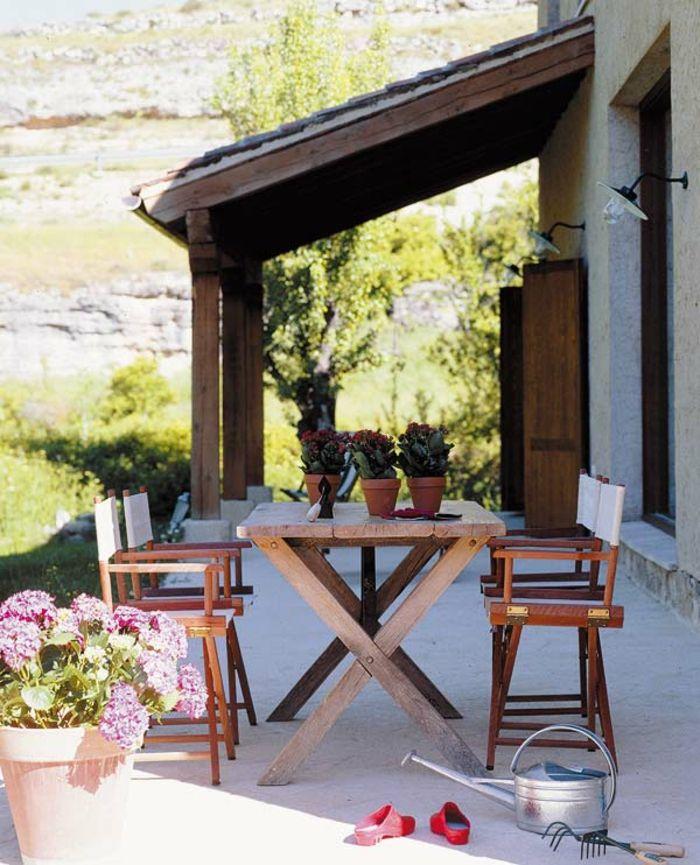 terrazas con encanto terraza con mesa y sillas de madera flores decoraticos y regadera