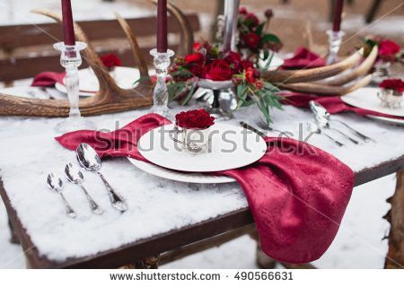 Wedding table setting in marsala colors with plates, cutlery, red floral compositions, candles, velvet napkins, deer horns on table covered with snow