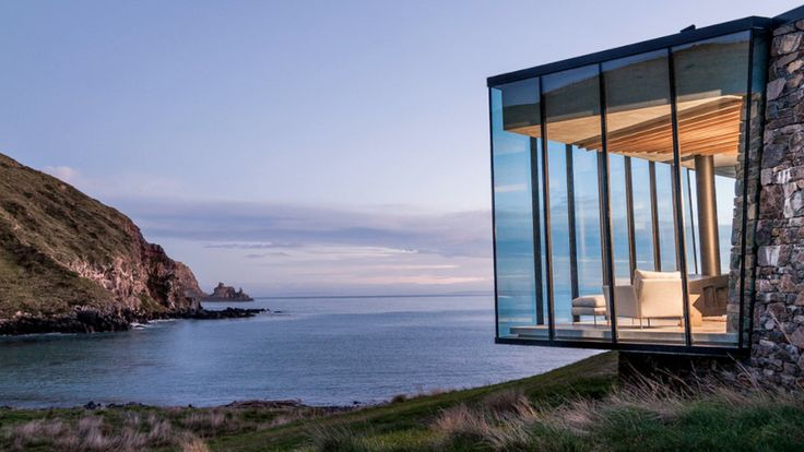 This glass-and-stone holiday home situated in a private bay frames stunning sea views with an expanse of windows that appears to perch above the cove.