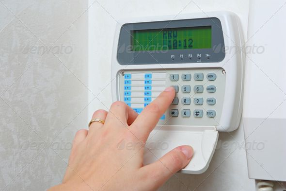 Female hand arming a burglar alarm system. http://photodune.net/item/alarm-in-house/494113