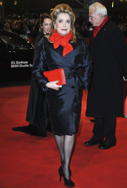 CATHERINE DENEUVE, 71. Never underestimate the power of a bold accessory. The legendary French actress dressed simply in demure black allows her clutch and scarf to make the high-impact statement.