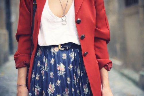 red coat, necklace, pleated skirt with belt