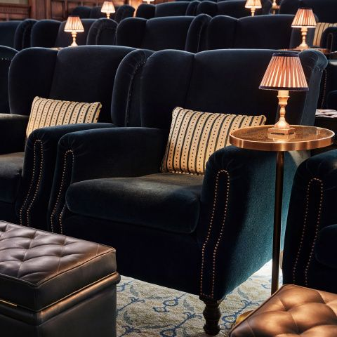You'll find our Cinema armchairs in the screening rooms in all the Houses, as well as our Electric cinemas. It's been designed to make watching a film as comfortable as possible, with 'ears' to support the head, the perfect seat depth and arm width for comfort. • Overstuffed velvet armchair with scatter cushion • Solid wood frame and brass stud trim • Handmade by skilled craftsmen in England • Used in all our Electric cinemas and screening rooms in the Houses • Matching footst...