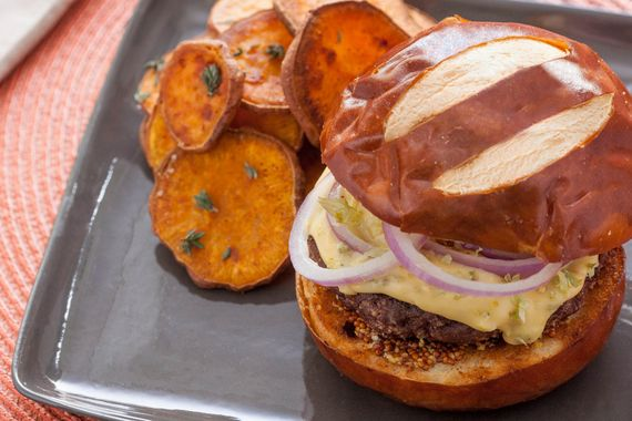 The once-humble burger gets a sophisticated makeover in this recipe. We're serving our burgers on soft pretzel buns, with red onion, whole grain mustard and a smooth cheddar sauce infused with a special ingredient: hops flowers. Only recently repurposed by chefs, hops are best known for imparting slightly bitter flavor to beer. Here, their floral bite acts as a perfect counterpoint to the rich cheddar and juicy beef. We're even updating the classic side of fries—roasting sweet potato rounds…