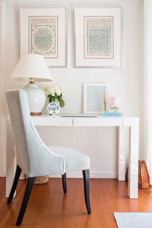 Chic home office boasts art over a West Elm Parsons Desk with Drawers topped with a pale blue ceramic lamp paired with a blue velvet chair.