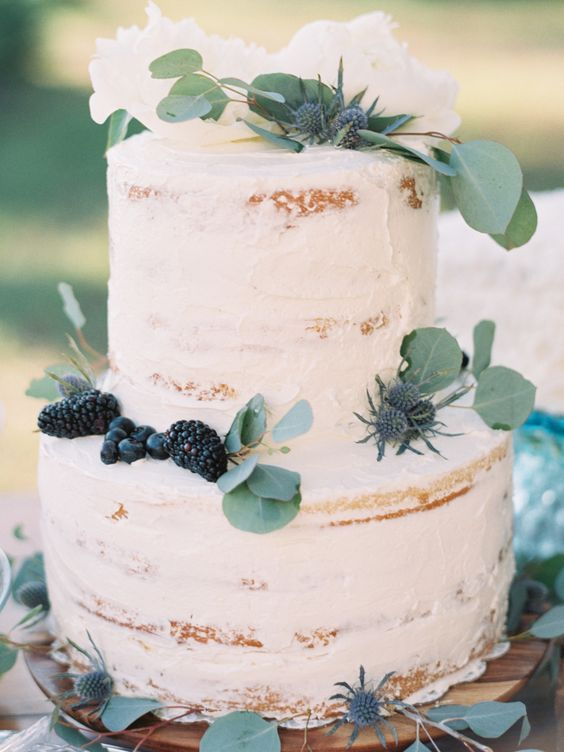 two tiered cake topped with greenery, blackberries and thistles