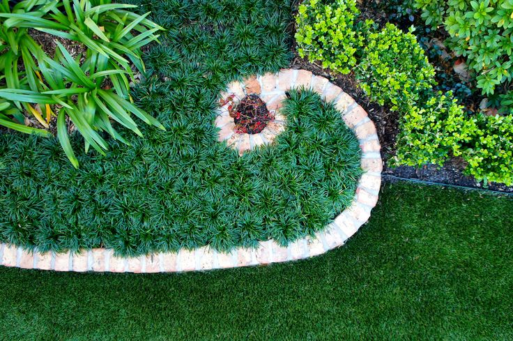 Decorative brick border curves around boxwood hedges and Dwarf Monkey Grass separating garden from synthetic lawn.