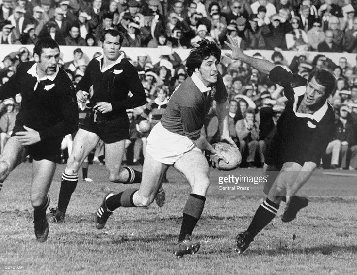Andy Irvine of the British Lions evades a tackle by Kevin Eveleigh of the New Zealand All Blacks, during the second rugby test match at Christchurch, New Zealand, 15th July 1977. Also in pursuit of Irvine are Bill Osborne and Lawrie Knight. The British Lions won the match 13-6.