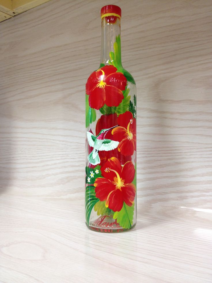 Red hibiscus with hummingbird on clear glass bottle.