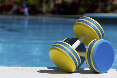 Plastic dumbbells for water aerobics by a swimming pool.