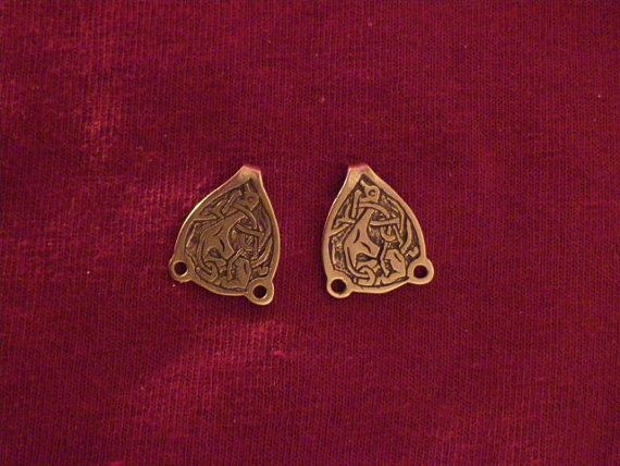 Pair of dress hooks with Trewhiddle style beast. Cast in brass and a little over 1/2 wide. Based on a 9th century piece.