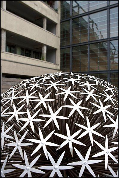 Detail of Urbansplash sculpture against backdrop of offices, Manchester