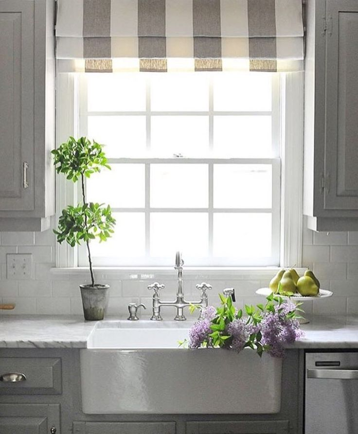 A Roman shade over a kitchen sink window offers a great touch of softness to all the hard surfaces in a kitchen.