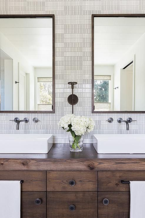 Alyssa Rosenheck - Jennifer Robin Interiors - Welcoming transitional bathroom features a stained oak dual apothecary style bath vanity accented with rectangular vessel sinks fixed beneath matte black faucets mounted to black and white modern tiles under dark stained oak framed mirrors.