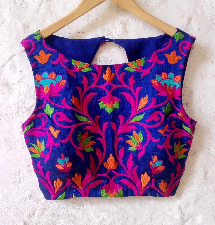 Questa camicetta di seta blu ha un complessivo popolare si sentono portati fuori dal pattern ricamo colorato. Il frontale ha tutto ricamo floreale in rosa, verde e colore arancio. La parte posteriore ha un contrasto dettaglio fucsia seta grezza. La chiusura è unapertura degli occhi n gancio sul retro. Questa camicetta versatile può essere combinata con sari colorati in rosa, blu o verde.  Si tratta di una camicetta imbottito in dimensioni (Large)---busto 38/ vita 32. La camicetta è dotat...