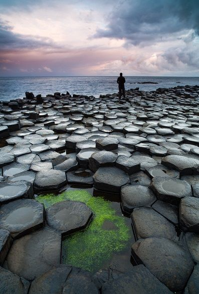 The Hexagons - Giant's Causeway is an area of about 40,000 interlocking basalt columns, the result of an ancient volcanic eruption. Located in Northern Ireland, it was declared a World Heritage Site by UNESCO in 1986. The tops of the columns form stepping stones that lead from the cliff foot and disappear under the sea. Most of the columns are hexagonal, although there are also some with four, five, seven or eight sides. Image by Thomas Mader.