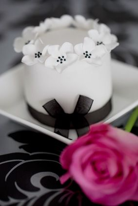 Mini Cake Guest Favor: For a monochrome theme, black and white blossoms decorate this pretty cake.  Mix and match with a co-ordinating cupcake design or fresh flowers to create a stunning centrepiece. Mini cakes are available in fruit, lemon, vanilla or chocolate.