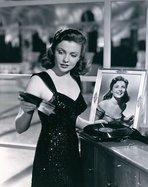 Joan Leslie flipping through some 78 rpm, 1953