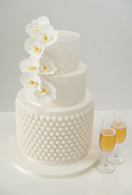Brides.com: . An all-white wedding cake will forever be in style. This chic, crisp-white version from Miso Bakes is embellished with mod, hexagon-shaped edible gemstones and cascade of sculptural phalaenopsis orchids handcrafted from sugar.   $12 per slice, Miso Bakes || #AislePerfect All White Wedding Cakes
