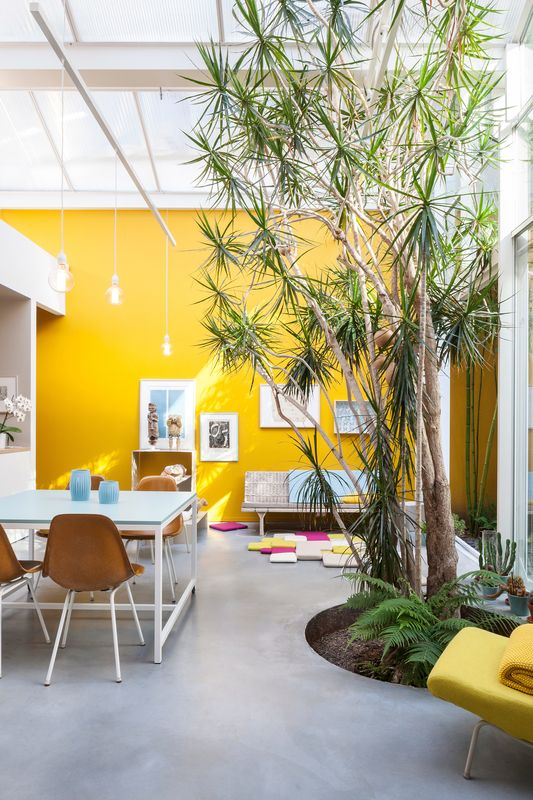 Furnished with vintage Eames chairs, a second-hand sofa, and pendants and tables designed by Nathalie, the space is kept purposefully casual. She painstakingly mixed and tested the paint for the mustard-yellow walls herself—15 times—to match the hue of a Kvadrat textile.