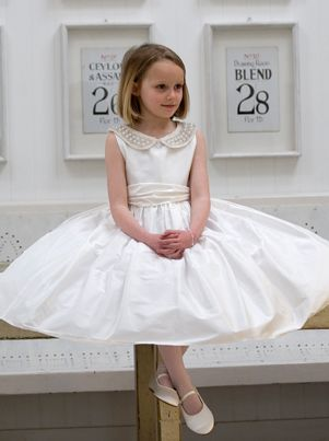 This beautiful silk First Holy Communion dress has a striking Peter Pan collar embellished with pearls and beads. By UK Royal Wedding designer Nicki Macfarlane.
