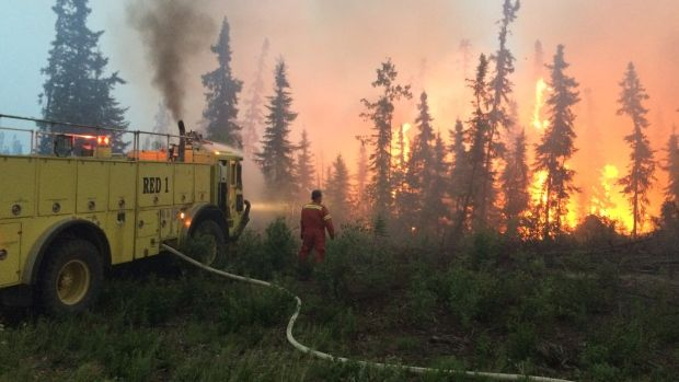 A firefighter battles the flames in the La Ronge, Sask. area on Saturday.