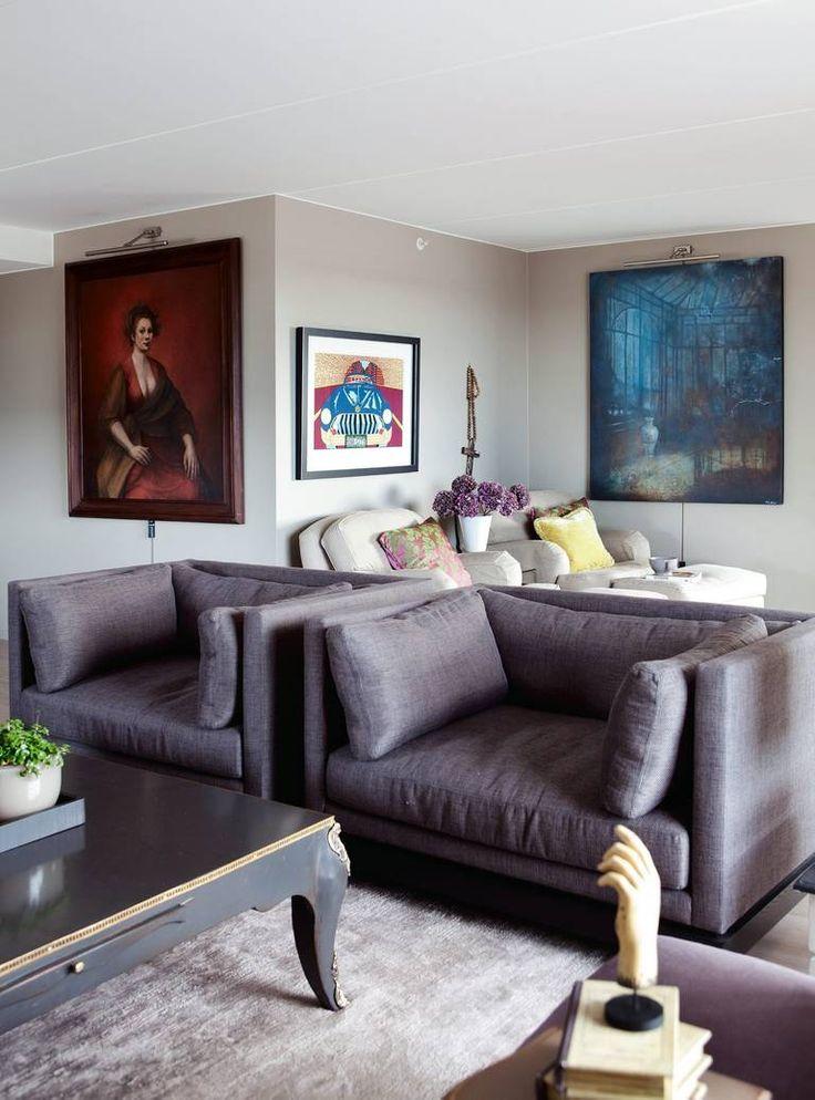 KUNST PÅ ALLE VEGGER: I tillegg til det mestnødvendige som lenestoler, sofa, bord og teppe, er stuen rikt møblert med kunst. Det store blå er signert Elisabeth Werp, i midten en Pushwagner, og det rødemaleriet er et selvportrett av kunstnerenTrine Folmoe. Hvite stoler fra Englesson og Verket Interiør, de lilla stolene er fra Christian's.