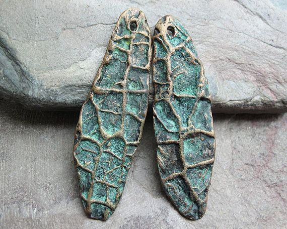 A pair of dangles with natural patterns, both sides. Finished with metallic bronze paint and chemical patina.    Approximately 2.25 long, by 17mm