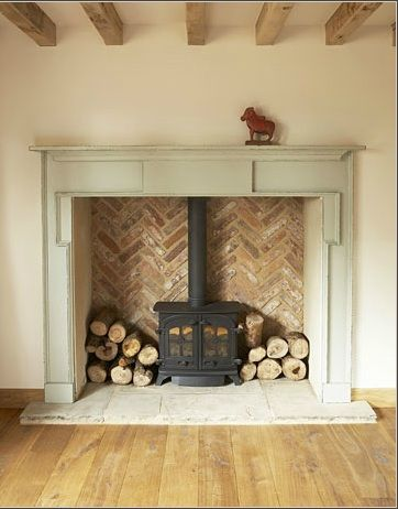 This is basically what I'm thinking... An antique fireplace mantle with either tile or brick in a herringbone pattern like this, but all elevated. It will be FAB