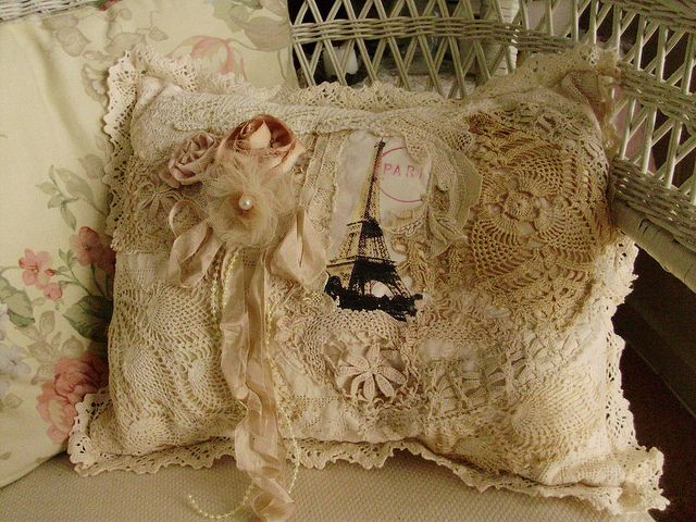 Pillow made of crocheted doilies, ribbon roses, and a picture of the Eiffel Tower on fabric.