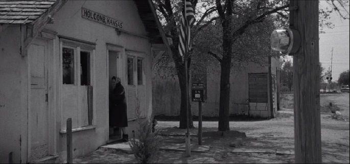 """""""La gente de Holcomb habla de su estafeta de correos llamándola Edificio Federal, lo que parece un título demasiado pomposo para designar una simple barraca expuesta al polvo y al viento. El techo tiene goteras, las tablas del suelo bailan, los buzones no cierran, las bombillas están rotas, el reloj, parado."""""""