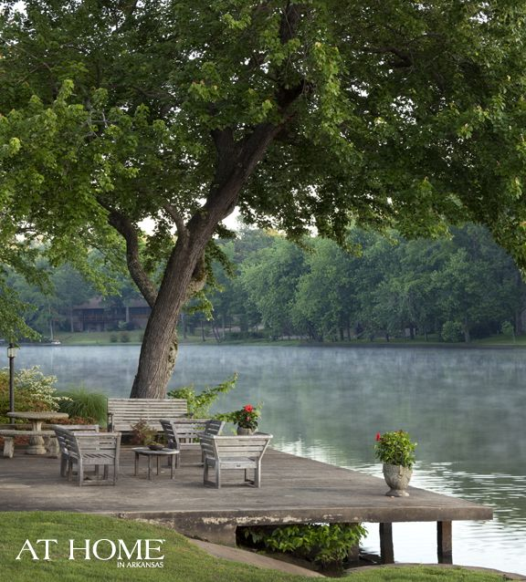 'Backyard Escape', via At Home in Arkansas. Photo by Nancy Nolan. On the dock, weathered teak furniture provides a place to take in the view of the North Little Rock lake.