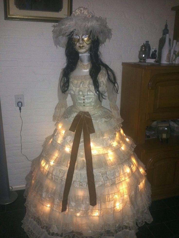 een ouderwetse jurk uit de jaren 20/30  en een venetiaans masker heeft ze op
