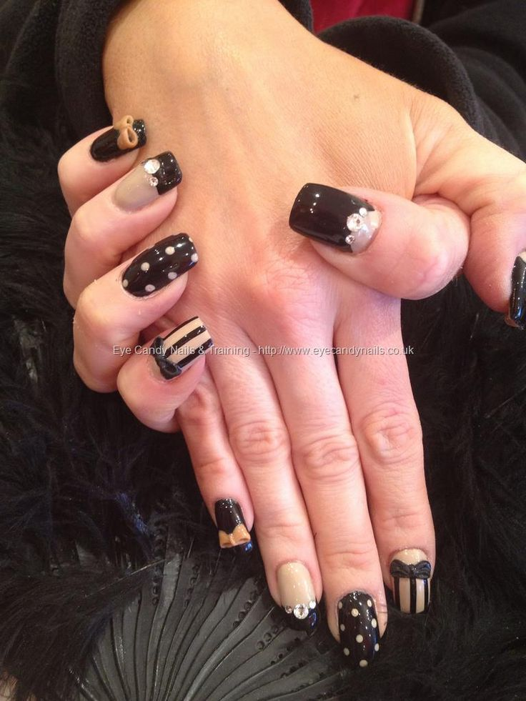 Nude and black freehand nail art with swarovski crystals and 3d bows over acrylic nails