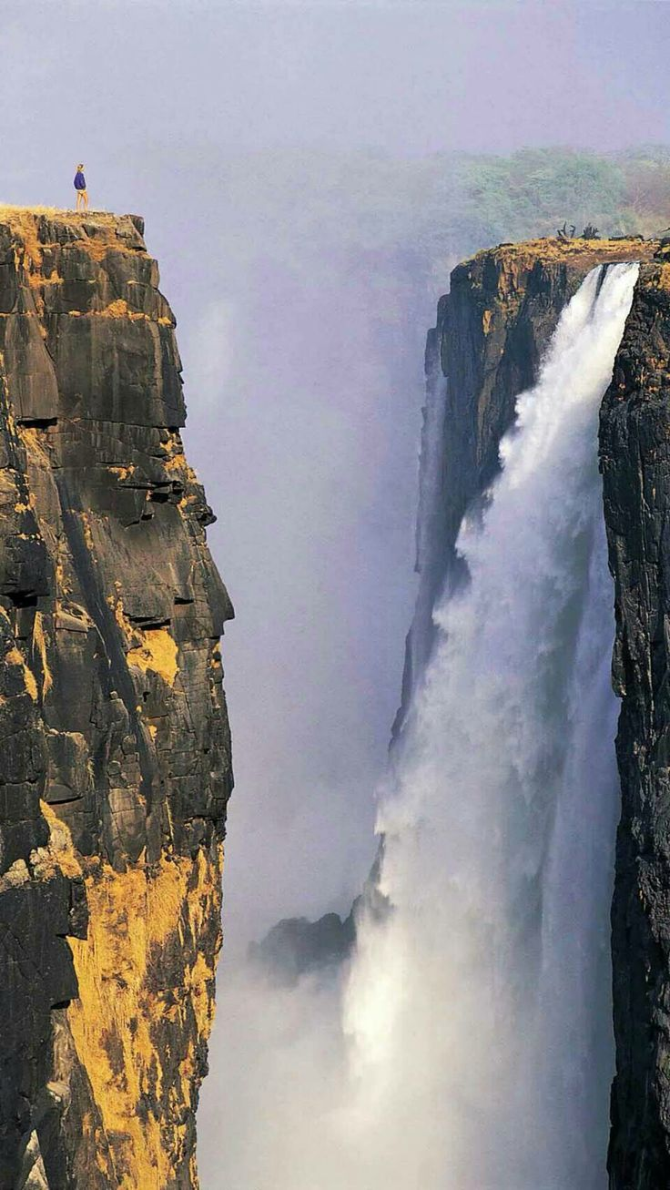 Victoria Falls, South Africa. Notice the miniscule tourists on the top of the gorge viewing the falls.