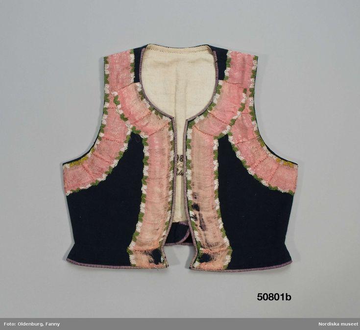 PRODUKTION 1820 - 1840 BRUKNINGSORT Sverige , Blekinge , Östra hd Av mörkblått kläde. 2 framstycken/sidstycken och ett ryggstycke, små infällda skörtkilar i sidorna och i ryggen 3 skörtveck. Kring alla kanter lila sidenband.