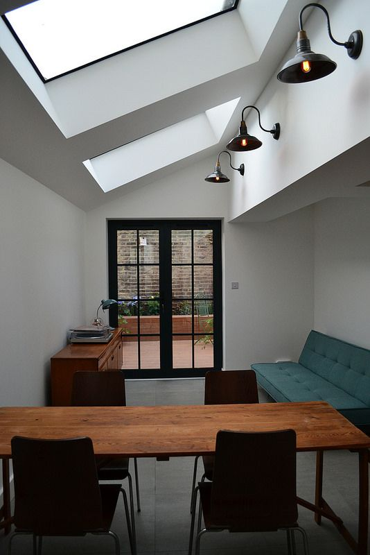 Side return extension in Stoke Newington, London by Shacklewell Architects. Industrial style lights from Industville, concrete style tiles from Fired Earth and doors from Durham Aluminium.