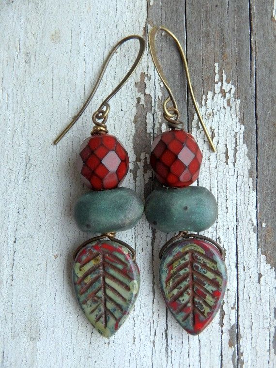 The ancient Greek and Romans wore laurel for protection and as a symbol of winning contests. Dainty Czech glass leaves hang from artisan ceramic nuggets in a dark verdigris green color. The leaves are streaked with rust red mirrored in the faceted Czech beads at the top. Czech glass leaves, Czech faceted glass and brass ear wires- Smitten Beads UK Ceramic nuggets- Kylie Parry Studios Hand patina copper wire- Artwear Elements  Measures: 2 from top of ear wire to bottom of the leaf.  To see…