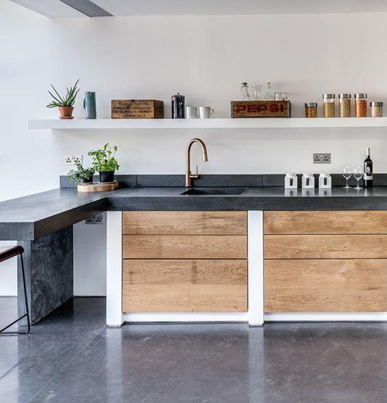 Темная бетонная кухонная столешница контрастирует со светлой древесиной кухонного фасада. .