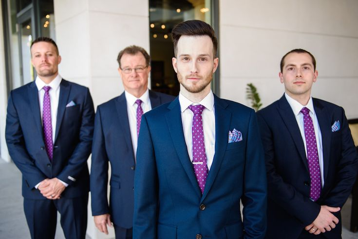 Wynston and his groomsmen looked dashing in navy blue suits accessorized with plaid pocket squares and purple ties featuring a unique pattern. #groomsmen #groomfashion Photography: Sarah & Ben. Read More: http://www.insideweddings.com/weddings/florida-wedding-celebration-with-vibrant-colors-and-wooden-details/644/