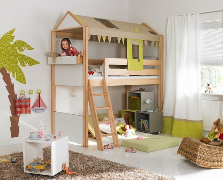 lit cabane en bois, boîtes de rangement et tapis shaggy gris dans la chambre de…