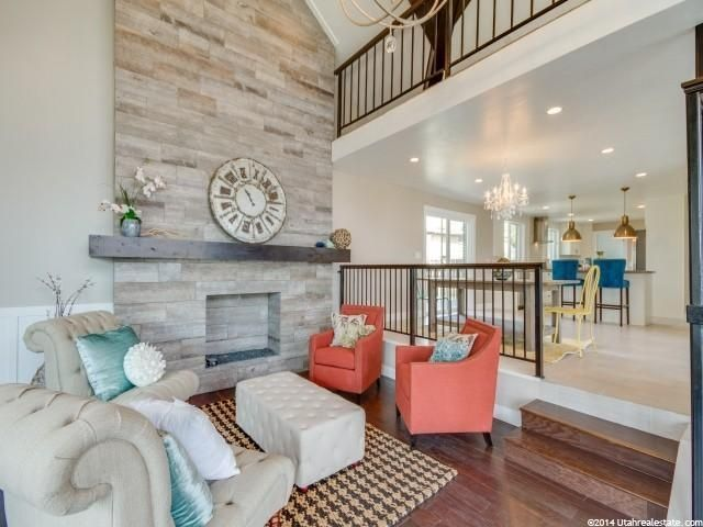 Contemporary Living Room With Chandelier Balcony Hardwood Floors Stone Fireplace Sunken